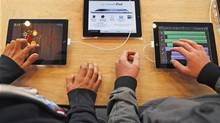 Customers try iPad tablets on display at an Apple store in Strasbourg, France. (VINCENT KESSLER/REUTERS)