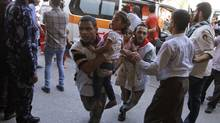 Palestinian medics carry children wounded in an attack on a UN school in Beit Hanoun, in the northern Gaza Strip on July 24, 2014. (Majed Hamdan/AP)