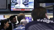 Traders from Knight Capital watch CEO Thomas Joyce give a television interview from the company's post on the floor of the New York Stock Exchange Aug. 2, 2012, after an erroneous trading position wiped out $440-million (U.S.) of its capital. (Brendan Mcdermid/Reuters)