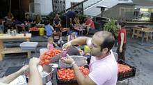 Chef Giacomo Pasquini pours tomatoes into a tomato-crushing machine while preparing tomato sauce with the help of his customers from Vertical Restaurant in Toronto. (Fernando Morales/The Globe and Mail)