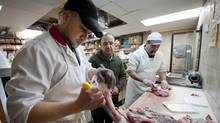 Ali Deis (centre) owner of Almizan Meat and Grocery in Montreal watches over Mourad, one of his butchers as he prepares Halal veal for sale at his grocery store. (Peter Mccabe/THE GLOBE AND MAIL)