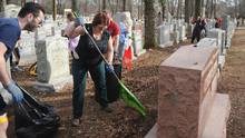 "Volunteers help during a cleanup effort at Chesed Shel Emeth Cemetery in University Cit after recent vandalism. Incidents like this one have the local Jewish community in ""heightened sense of alert."" (Michael Thomas/Getty Images)"