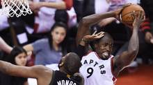 Toronto Raptors forward Serge Ibaka (9) grabs a rebound in front of Milwaukee Bucks centre Greg Monroe (15) during second half NBA playoff basketball action, in Toronto on Saturday, April 15, 2017. (Nathan Denette/THE CANADIAN PRESS)