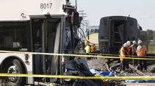 Investigators examine the scene of an accident involving a bus and a train in Ottawa on Sept. 18, 2013. (CHRIS WATTIE/REUTERS)