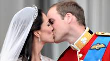 Britain's Prince William kisses his wife Kate, Duchess of Cambridge, on the balcony in Buckingham Palace, after the wedding service, on April 29, 2011, in London. (Leon Neal/AFP/Getty Images)