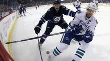 Winnipeg Jets' Andrew Copp battles Vancouver Canucks' Henrik Sedin on March 26, 2017. (Trevor Hagan/The Canadian Press)
