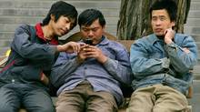 Chinese migrant workers use a cell phone in Beijing (ELIZABETH DALZIEL/Elizabeth Dalziel/AP)