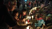 Ted Engelmann, left, helps Yamilet Ortega, 3, second from left, and Kimberly Hernandez, 7, light candles, Saturday, July 21, 2012, at a memorial near the movie theater in Aurora, Colo. where a gunman killed at least 12 people and wounded dozens of others Friday in one of the deadliest mass shootings in recent U.S. history. (Ted S. Warren/AP)