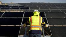 A worker installs First Solar Inc. photovoltaic solar panels at the Agua Caliente Solar Project in Yuma County, Arizona. (Joshua Lott/Bloomberg)