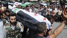 People carry a body of a person killed in clashes in Aleppo, Syria, Friday, July 27, 2012. (Alberto Prieto/Associated Press)