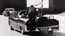 President John F. Kennedy slumps down in the back seat of the presidential limousine after being fatally shot in Dallas on Nov. 22, 1963. Mrs. Jacqueline Kennedy leans over the president while a Secret Service agent stands on the bumper. (IKE ALTGENS/AP)