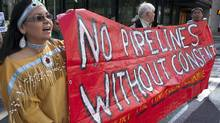 Natives from the Yinka Dene Alliance march through downtown Calgary in May to protest Enbridge Pipeline's Northern Gateway project. (Jeff McIntosh/THE CANADIAN PRESS)
