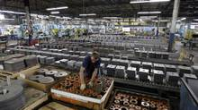 An employee at Baldor Electric Co. works inside the company's factory in St. Louis. (Jeff Roberson)