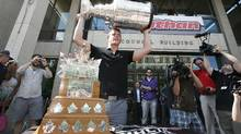 Jonathan Toews raises the Stanley Cup in front of the Conn Smythe trophy for being named playoff MVP after being honoured at city hall in Winnipeg, Sunday. (John Woods/The Canadian Press)