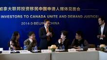 Immigration consultant Larry Wang, centre, speaks to Chinese millionaires on March 4, 2014, as they make a plea to the Canadian government to ditch its plans to end its backlogged investor immigrant program. (Andy Wong/Associated Press)