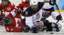 Canada's Kevin Rempel and Billy Bridges fight for the puck with Nikko Landeros of the U.S during the semi-final sledge hockey game at the 2014 Sochi Winter Paralympic Games March 13, 2014. (ALEXANDER DEMIANCHUK/REUTERS)