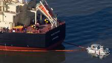 A spill response boat secures a boom around the cargo ship MV Marathassa after a bunker fuel spill on Burrard Inlet in Vancouver, B.C., on April 9, 2015. One former maritime lawyer said if the U.S. Coast Guard ranked an eight or nine out of 10 worldwide, then Canada's Coast Guard would rank a one or two. (DARRYL DYCK/THE CANADIAN PRESS)