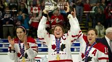 Team Canada captain Hayley Wickenheiser hoists the championship trophy with the help of teammates Caroline Ouellette, left, and Brianne Jenner after defeating Team USA in the gold medal final game at the World Women's Ice Hockey Championships Saturday, April 14, 2012 in Burlington, Vermont. THE CANADIAN PRESS/Paul Chiasson (Paul Chiasson/CP)