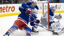 New York Rangers left winger Brandon Prust (left) is hauled down by Toronto Maple Leafs centre Mikhail Grabovski as he closes on goaltender Jonas Gustavsson during first period NHL hockey action in Toronto on Thursday October 21, 2010. (Frank Gunn)