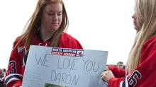 Alison Greene (left) and Brigite Baker (right) hold up a sign in memory of their former teammate Daron Richardson prior to a memorial service at ScotiaBank Place in Ottawa on Wednesday, November 17, 2010. Richardson, the 14-year-old daughter of Ottawa Senator's assistant coach Luke Richardson, died last week. (Pawel Dwulit/Pawel Dwulit/The Canadian Press)