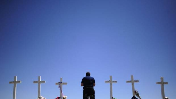 "Travis Hirko kneels in front of the cross for Alex Sullivan at a memorial at in Aurora, Colo. on Sunday, July 22, 2012. Hirko went to high school with Sullivan, a victim of Friday's shooting rampage during a midnight showing of ""The Dark Knight Rises"" in Aurora. (AAron Ontiveroz/AP)"
