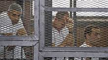 In this Thursday, May 15, 2014 file photo, from left, Mohammed Fahmy, Canadian-Egyptian acting bureau chief of Al-Jazeera, Australian correspondent Peter Greste, and Egyptian producer Baher Mohamed appear in a defendant's cage along with several other defendants during their trial on terror charges at a courtroom in Cairo. Egypts state news agency says the trial of three Al-Jazeera English journalists and 17 others has adjourned until next week when the judge will deliver the verdict, five months after the trial opened. Fahmy, Greste and Baher have been in detention since December 29. (Hamada Elrasam/AP)