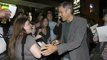 Actor George Clooney is greeted by fans after dining in Toronto.