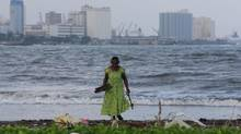 An elderly Sri Lankan woman collects pieces of wood in the sea promenade of Colombo port, in Colombo, Sri Lanka, Wednesday, Oct. 2, 2013. (Eranga Jayawardena/Associated Press)