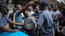 South African police officers detain a Nigerian man during a face-off with a group of South Africans in the centre of Pretoria on February 24, 2017. South African police fired rubber bullets and stun grenades to break up clashes between local protesters and migrants in Pretoria on February 24 at a march against immigration. (MARCO LONGARI/AFP/Getty Images)