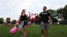 Audrey Lafond, right, and her spouse, Cedrick Billequey, play with their 2-year-old daughter, Juliette, at a soccer game in Laval-des-Rapides, Que., Aug. 21, 2012. (Christinne Muschi For The Globe and Mail)
