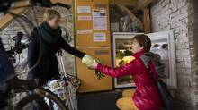 Two women at a food-sharing refrigerator, usually filled with leftovers from private parties and restaurants, in Berlin, Nov. 26, 2014. (GORDON WELTERS/New York Times)