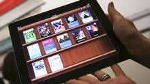A woman holds up an iPad with the iTunes U app after a news conference introducing a digital textbook service in New York in this January 19, 2012, file photo. (SHANNON STAPLETON/REUTERS)