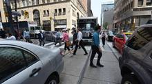 Pedestrians and vehicular traffic clog a Toronto intersection. (Fred Lum/The Globe and Mail)