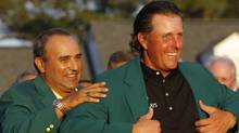 Phil Mickelson (R) of the U.S. is helped into the green jacket by last year's champion Angel Cabrera of Argentina after winning the 2010 Masters golf tournament at the Augusta National Golf Club in Augusta, Georgia, April 11, 2010. REUTERS/Hans Deryk (HANS DERYK)