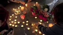 People gather at a memorial honouring teen Amanda Todd in Maple Ridge, B.C., on Monday. (JONATHAN HAYWARD/THE CANADIAN PRESS)