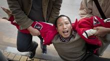 Xiao Qingshan, a protestor outside the newspaper office Southern Weekend, is taken away by undercover police in Guangzhou, January 10, 2013. Mr. Obama will speak to human-rights issues in China and military operations in the Pacific during his meeting with President Xi Jingping. (John Lehmann/The Globe and Mail)