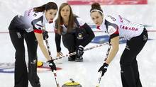 Canada's Lisa Weagle, left, and Joanne Courtney, right, sweep a path for the stone as Rachel Homan, center, watches at World Women's Curling Championship 2017 in Beijing, March 23, 2017. (Mark Schiefelbein/THE ASSOCIATED PRESS)
