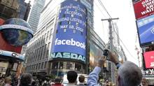A man stops to photograph Nasdaq in Times Square as Facebook has its IPO, Friday, May 18, 2012, in New York. (Richard Drew/AP Photo/Richard Drew)
