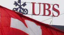 Two Swiss flags fly above a logo of the UBS on the top of the Swiss banking giant headquarters, on November 15, 2008 in Zurich. (FABRICE COFFRINI/AFP/Getty Images)