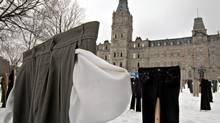 Pants with turned-out pockets hang outside the National Assembly building in Quebec City on Tuesday, as part of a radio-station stunt to protest against the provincial budget. The station also encouraged passersby to turn out their pockets and passing drivers to honk their horns. (Jacques Boissinot/The Canadian Press)