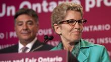 Ontario Premier Kathleen Wynne is framing issues in terms of job creation and the economy, instead of social justice. She is pictured here with Finance Minister Charles Sousa appear at a press conference following the passing of the provincial budget at Queen's Park June 11, 2013. (Moe Doiron/The Globe and Mail)