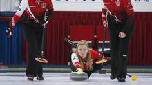 Team Canada skip Chelsea Carey, centre, makes a shot as her teammates, second Jocelyn Peterman, left, and lead Laine Peters, train in Calgary, Alta., on Feb. 13, 2017. (Jeff McIntosh/THE CANADIAN PRESS)