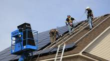 Workers install solar rooftop panels in this handout photo. (Handout/Pure Energies Group Inc.)