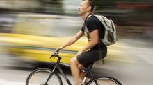 A cyclist makes his way along the bike lane at corner of Hornby st. and Robson St. in Vancouver June 27, 2011. (John Lehmann/The Globe and Mail/John Lehmann/The Globe and Mail)