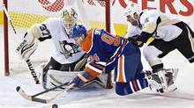 Pittsburgh Penguins' Jeff Zatkoff makes the save on Edmonton Oilers' Ryan Smyth as Rob Scuderi defends during third period NHL hockey action in Edmonton, Alta., on Friday January 10, 2014. (JASON FRANSON/THE CANADIAN PRESS)