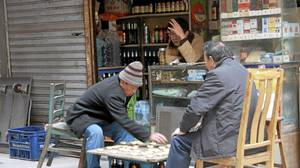 Local shopkeepers pass the time on the streets of the Bund neighbourhood.