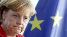 German Chancellor Angela Merkel stands in front of European Union flag (TOBIAS SCHWARZ)