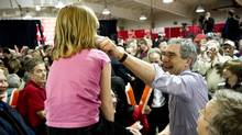 Michael Ignatieff pinches a young girl's cheek as she sits on the father's shoulders during a rally Saturday, April 23, 2011 (Paul Chiasson/Paul Chiasson/The Canadian Press)