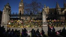The shadows of onlookers are cast on floral tributes to the victims of the March 22 terror attack pushed through the railings of the Houses of Parliament in central London on March 25, 2017. (DANIEL LEAL-OLIVAS/AFP/Getty Images)
