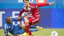 Montreal Impact's Hassoun Camara holds onto FC Dallas Conor Shanosky while fighting for the ball during first half MLS action in Montreal Saturday, July 20, 2013. (Peter Mccabe/THE CANADIAN PRESS)